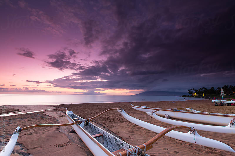 Canoes on the beach in a Hawaiien sunset by Chris Chabot for Stocksy United
