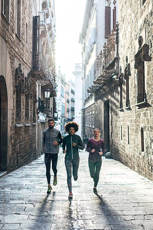 Group of young friends running on Barcelona streets. by BONNINSTUDIO for Stocksy United