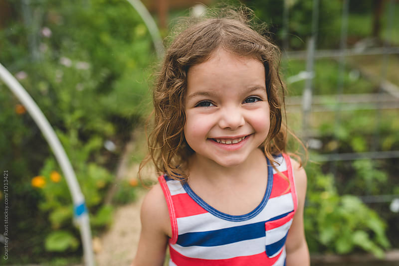 Smiling young girl in the garden  by Courtney Rust for Stocksy United