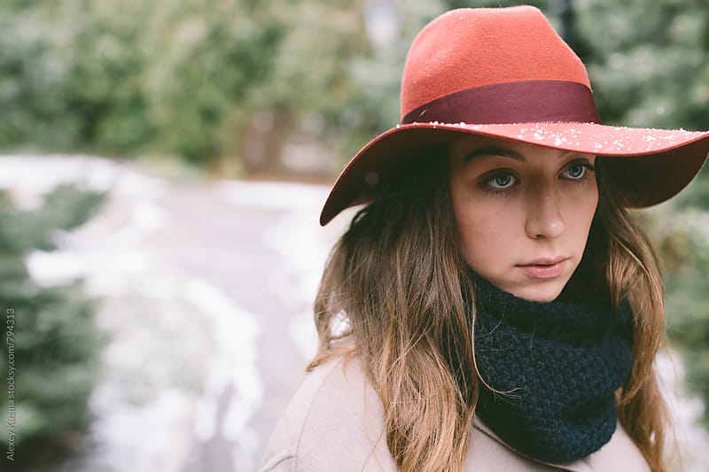 winter portrait of young woman with red hat outdoors by Alexey Kuzma for Stocksy United