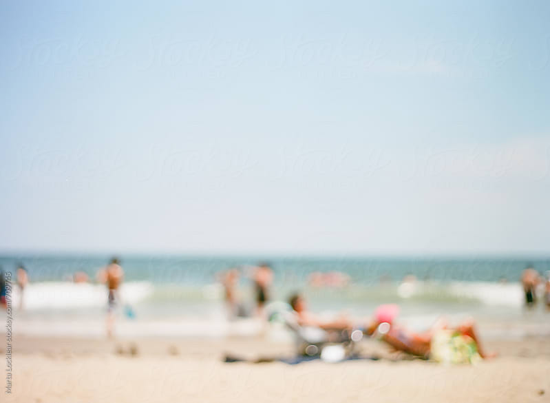 Blurred image of beach goers by Marta Locklear for Stocksy United