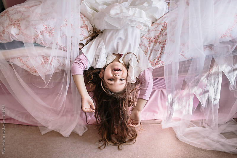 Little girl playing on bed by Peter Meciar for Stocksy United
