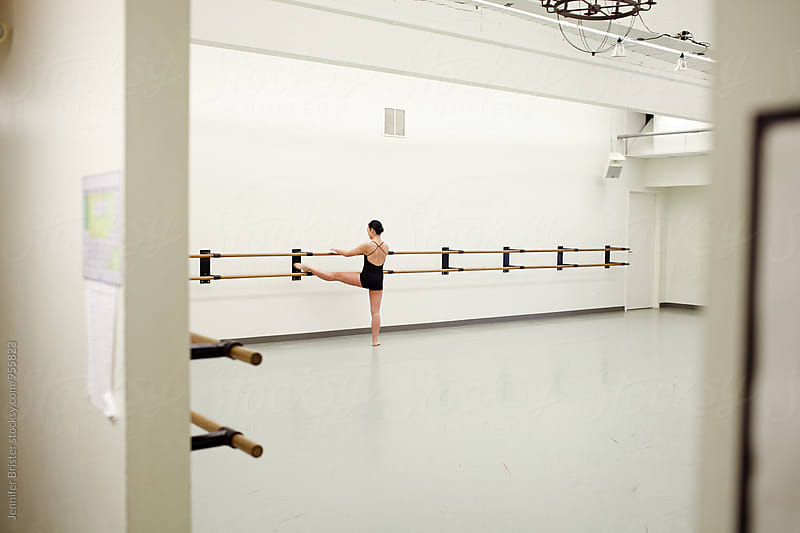 A woman stretching in dance studio by Jennifer Brister for Stocksy United