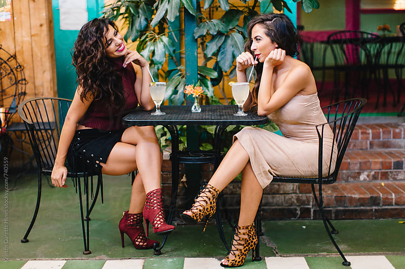 Two woman friends having cocktails at an outdoor mexican patio restaurant by Kristen Curette Hines for Stocksy United