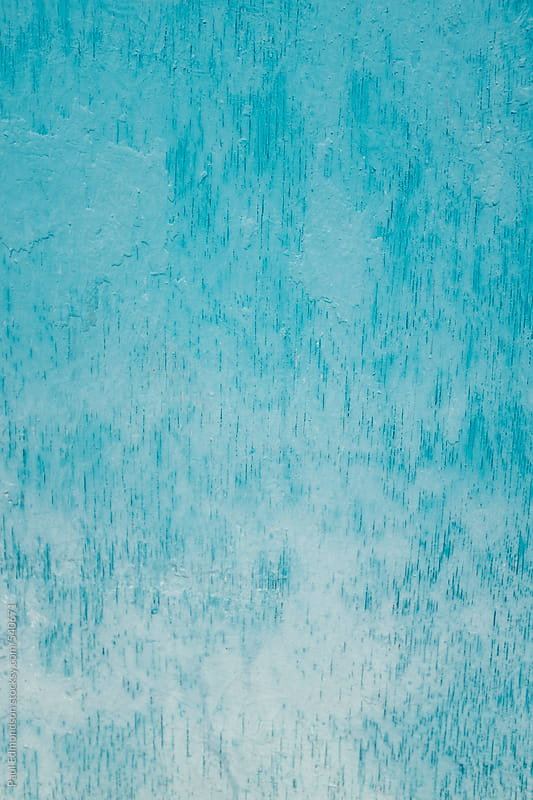 Close up of blue and turquoise paint covering graffiti on plywood wall by Paul Edmondson for Stocksy United