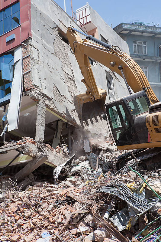 An excavator clearing debris of a fallen building after an earthquake. by Shikhar Bhattarai for Stocksy United