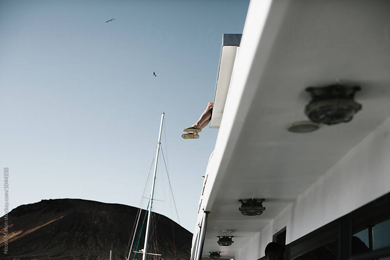 feet hanging over the edge of a boat by Nicole Mason for Stocksy United