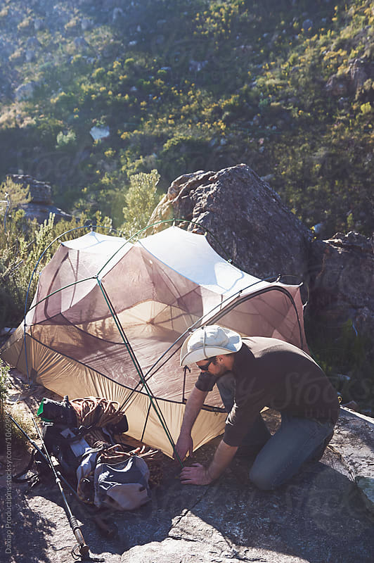 Erecting tent man by Daxiao Productions for Stocksy United
