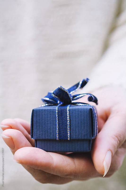 Hands holding gift  by Pixel Stories for Stocksy United