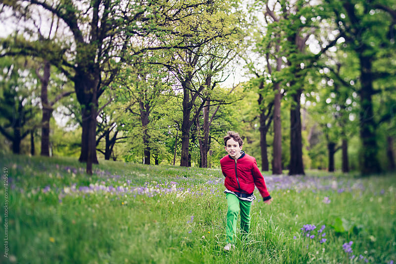 Boy running through field of bluebells by Angela Lumsden for Stocksy United