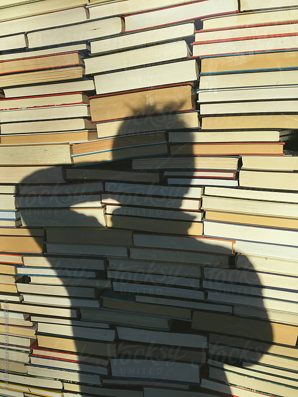 Stack of books and photographer's shadow by Paul Edmondson for Stocksy United