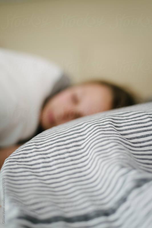 tween girl asleep on pillow in bed, defocussed leaving copyspace by Gillian Vann for Stocksy United
