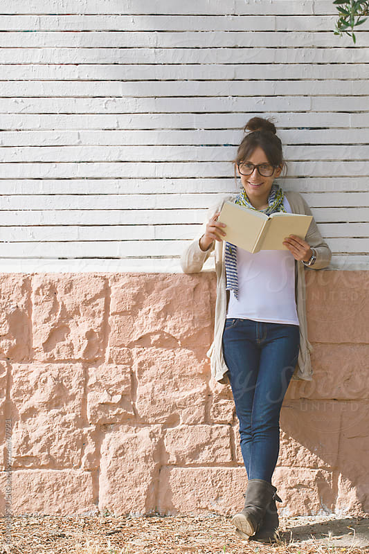 Young casual student woman reading in front a outdoors brick wall. by BONNINSTUDIO for Stocksy United