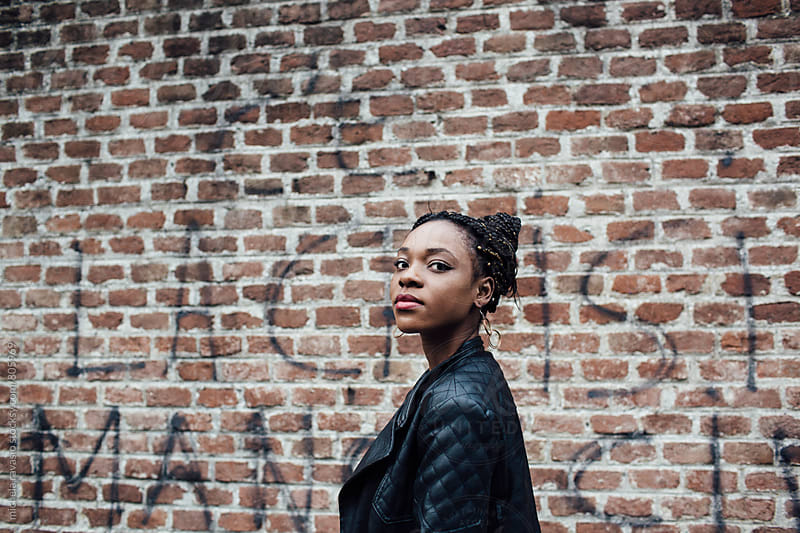 Young African woman walking along a brick wall by michela ravasio for Stocksy United
