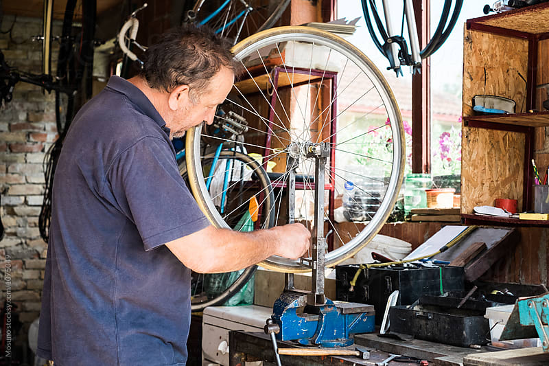 Senior Man Repairing a Wheel by Mosuno for Stocksy United