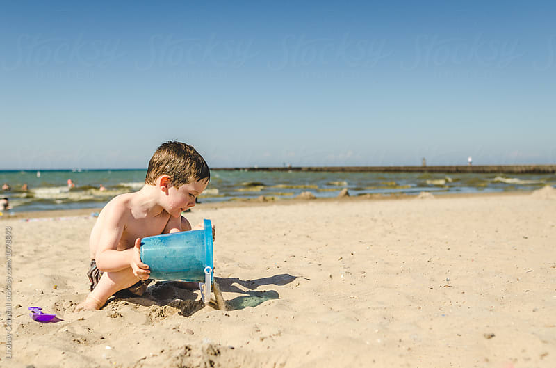 Boy dumping sand out of a bucket at the beach by Lindsay Crandall for Stocksy United