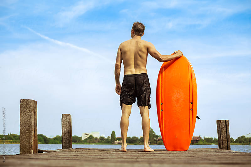 Young man looking on the lake with his board next to him by Jovo Jovanovic for Stocksy United