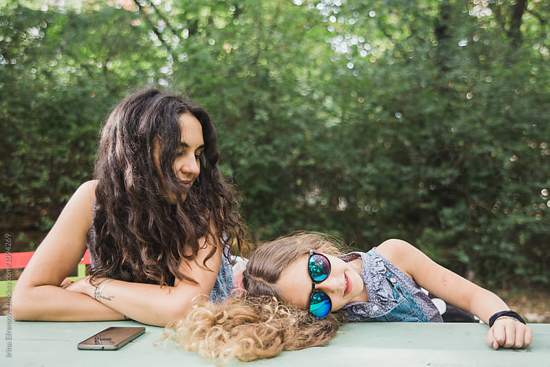Tired 6 years old girl laying on the table wearing sunglasses next to her mother by Irina Efremova for Stocksy United