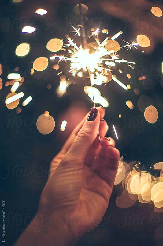 Female Hand Holding a Sparkler by Lumina for Stocksy United