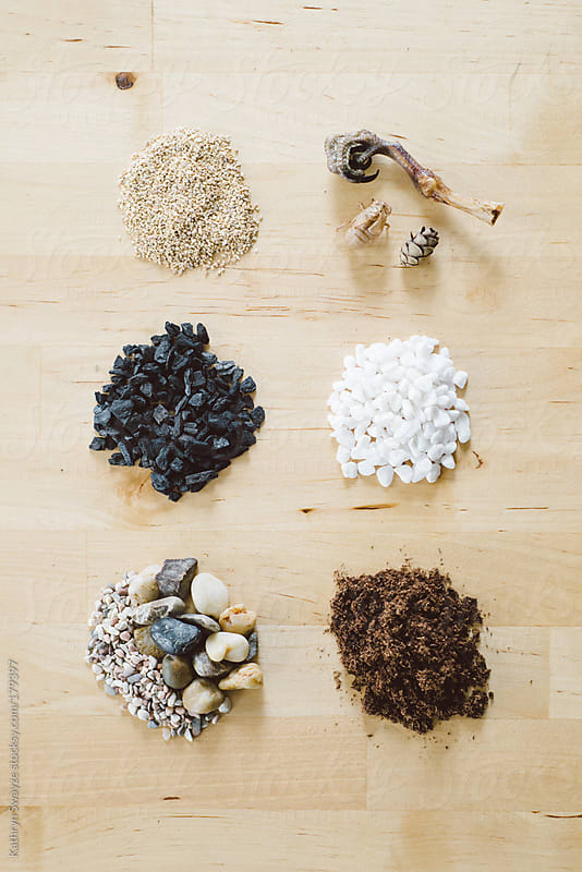 Sand, Charcoal, Pebbles, and Potting Soil Mix arranged in piles on a table. by Kathryn Swayze for Stocksy United