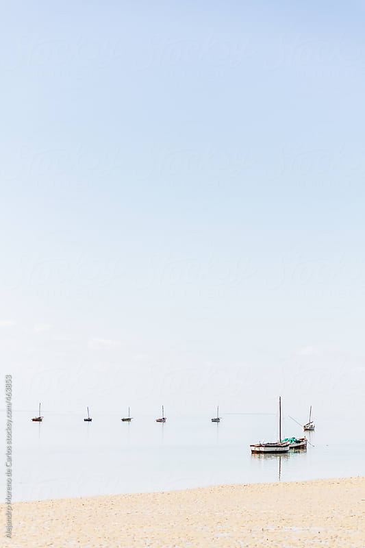 Boats on a calm tropical beach. Vertical shot with copyspace by Alejandro Moreno de Carlos for Stocksy United