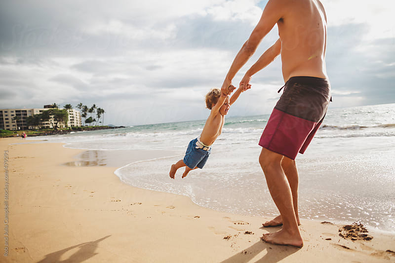 Young dad swinging his son around on tropical beach by Rob and Julia Campbell for Stocksy United