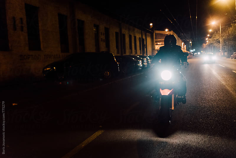 Man riding a bike on empty streets by night by Boris Jovanovic for Stocksy United