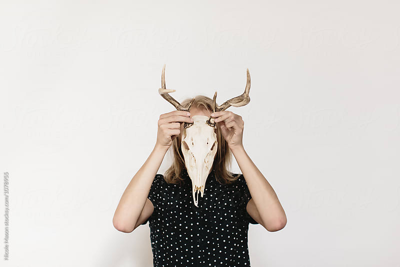 person holding deer skull in front of face with both hands by Nicole Mason for Stocksy United
