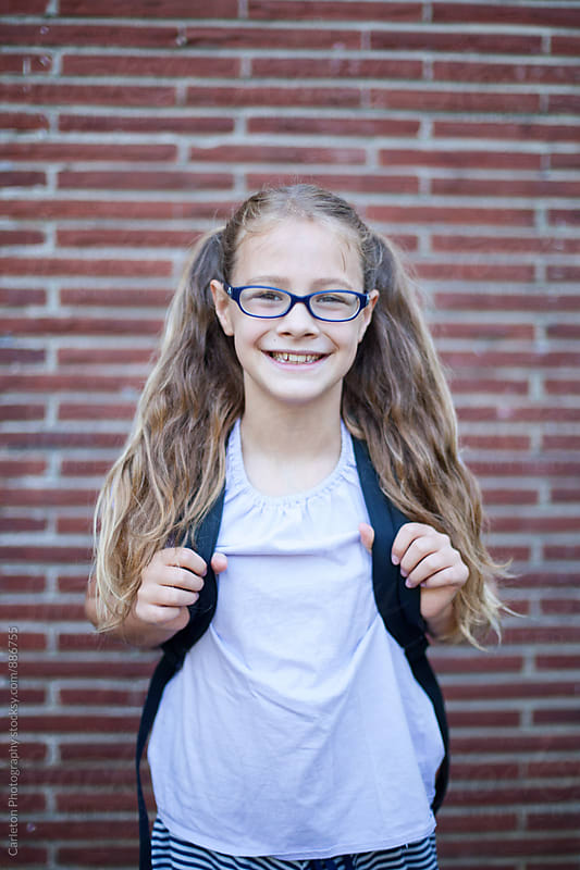 Schoolgirl with long hair in ponytails is ready for school by Carleton Photography for Stocksy United