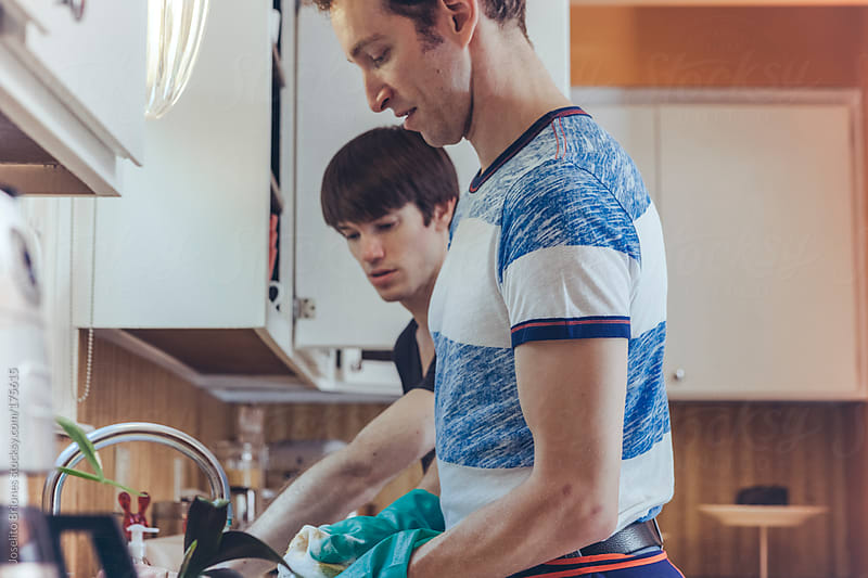 Gay Couple Doing Domestic Chore of Washing Dishes in Kitchen at Home by Joselito Briones for Stocksy United