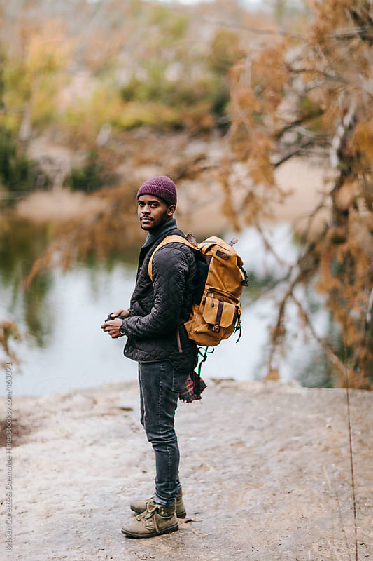 Male explorer outside enjoying nature on a cold rainy day by Kristen Curette Hines for Stocksy United