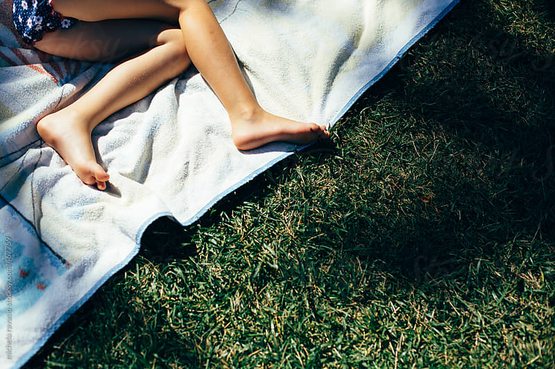 Legs of baby girl lying on a lawn by michela ravasio for Stocksy United