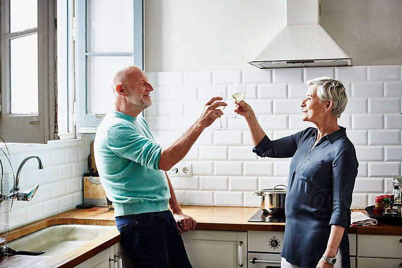 Senior Couple Toasting Wine Glasses In Kitchen by ALTO IMAGES for Stocksy United