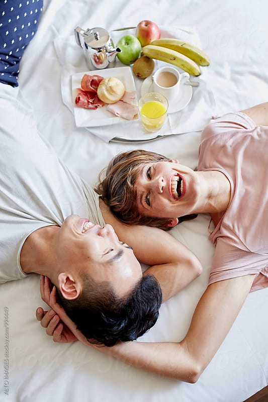 Happy Couple Lying By Breakfast Tray On Bed by ALTO IMAGES for Stocksy United