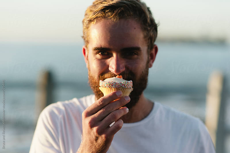 Man enjoying cupcake by Bruce and Rebecca Meissner for Stocksy United