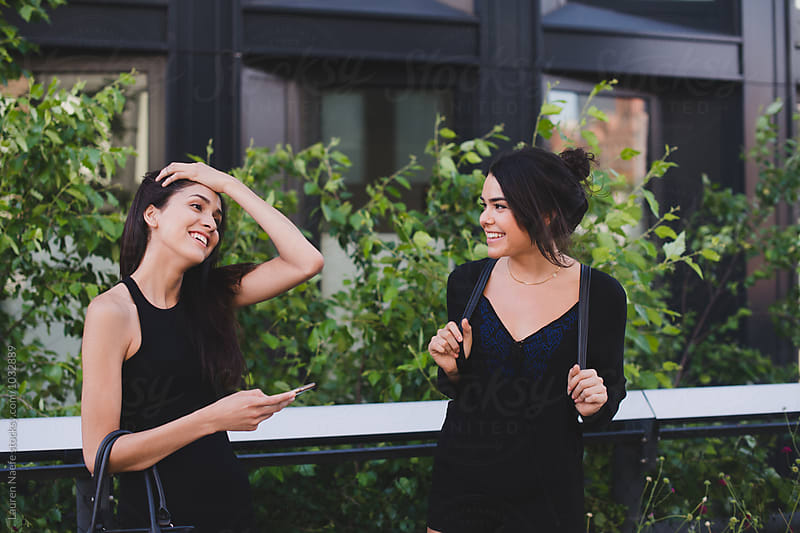 Friends laughing together outside by Lauren Naefe for Stocksy United