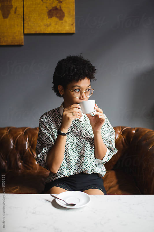 Woman drinking a coffee on a sofa  by michela ravasio for Stocksy United