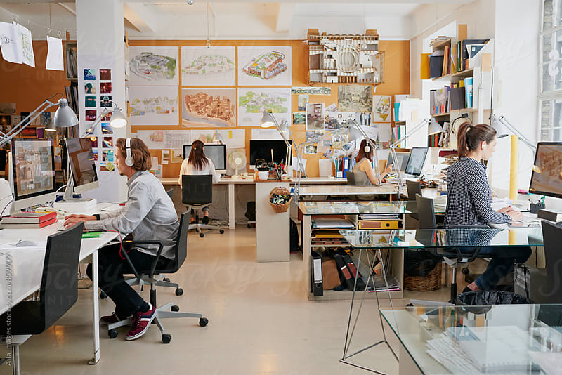 Busy architects office with architects working at computers by Aila Images for Stocksy United