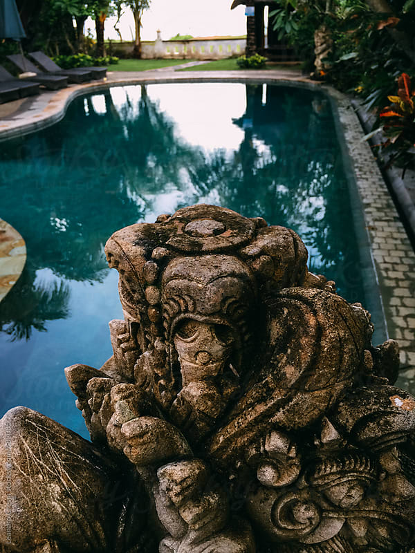 Ancient indonesian sculpture decorating a hotel swimming pool by Leandro Crespi for Stocksy United
