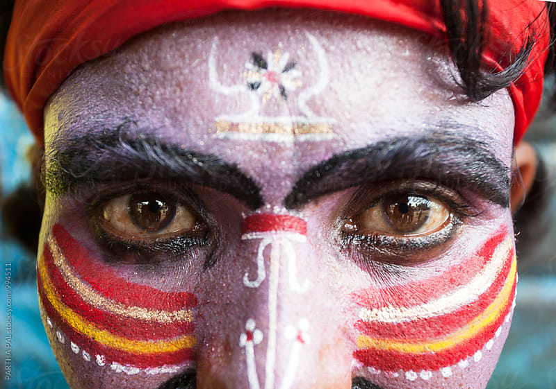 Close view of an Indian man with painted face by PARTHA PAL for Stocksy United