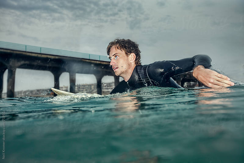 Man surfing in ocean by Neil Kremer for Stocksy United