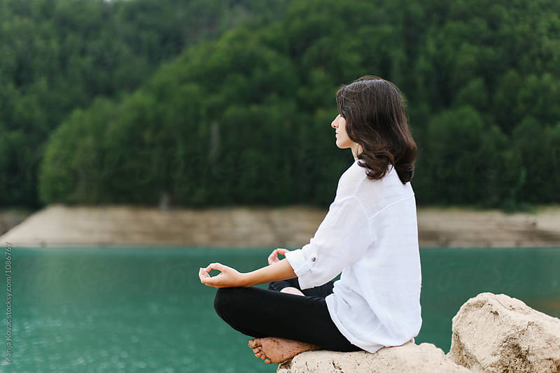 Woman meditating, sitting on the rock by Marija Kovac for Stocksy United