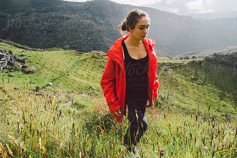 Girl with Red Jacket Walking through a Field by Oscar Lopez for Stocksy United
