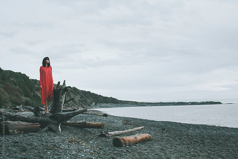 A woman in a red dress looking out to the ocean by Ania Boniecka for Stocksy United