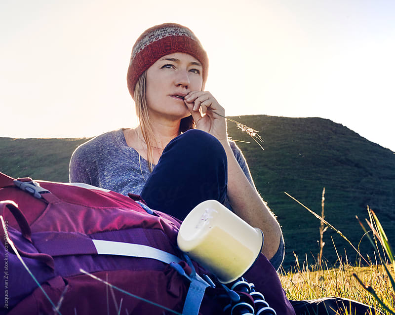 Female hiker with her back pack taking a break in a field surrounded by mountains. by Jacques van Zyl for Stocksy United
