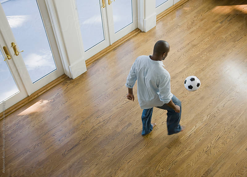 Man kicking soccer ball at home by Andersen Ross Photography for Stocksy United