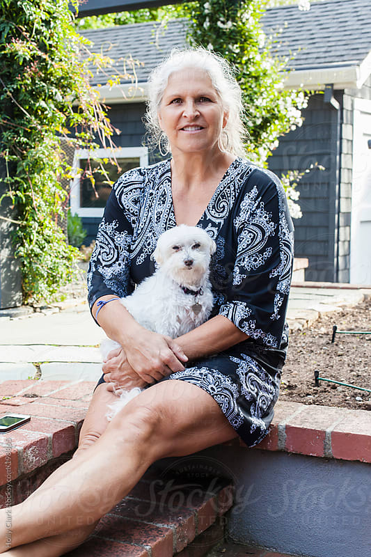 A beautiful silver-haired woman holds her pet dog in the garden. by Holly Clark for Stocksy United