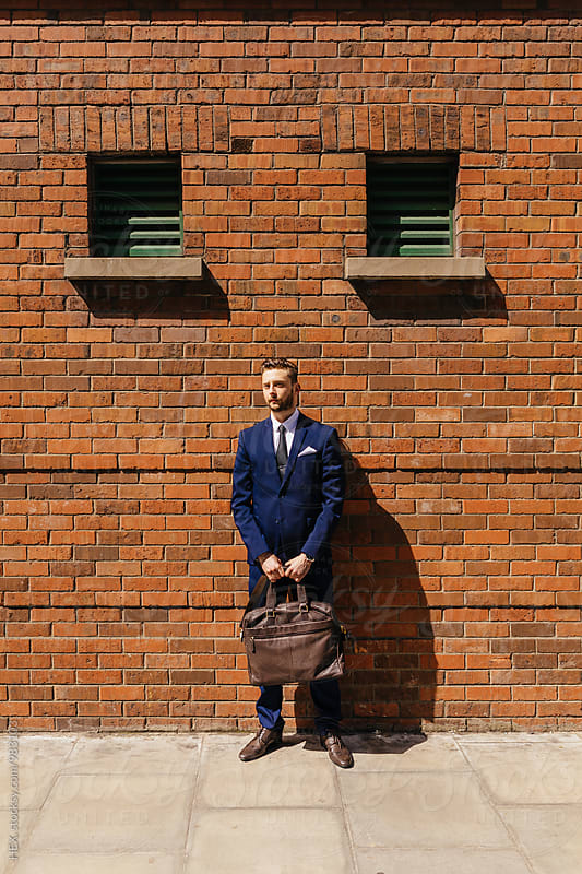 Portrait of a young businessman holding his briefcase standing on the street. by HEX. for Stocksy United