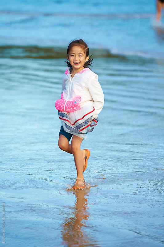 happy little girl playing on beach  by Bo Bo for Stocksy United