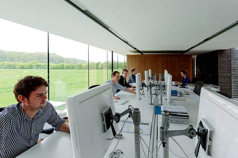 Modern office with five employees working by Paul Phillips for Stocksy United